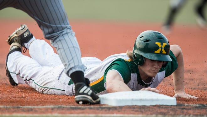 St. Xavier's Sam Wilson dives back safely to first base during a game against Pleasant Ridge Park on Wednesday evening at St. Xavier. May 10, 2017