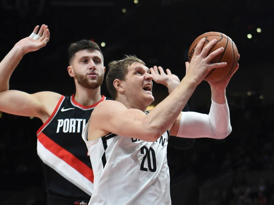 Brooklyn Nets center Timofey Mozgov drives to the basket on Portland Trail Blazers center Jusuf Nurkic during the first half of an NBA basketball game in Portland, Ore., Friday, Nov. 10, 2017. (AP Photo/Steve Dykes)