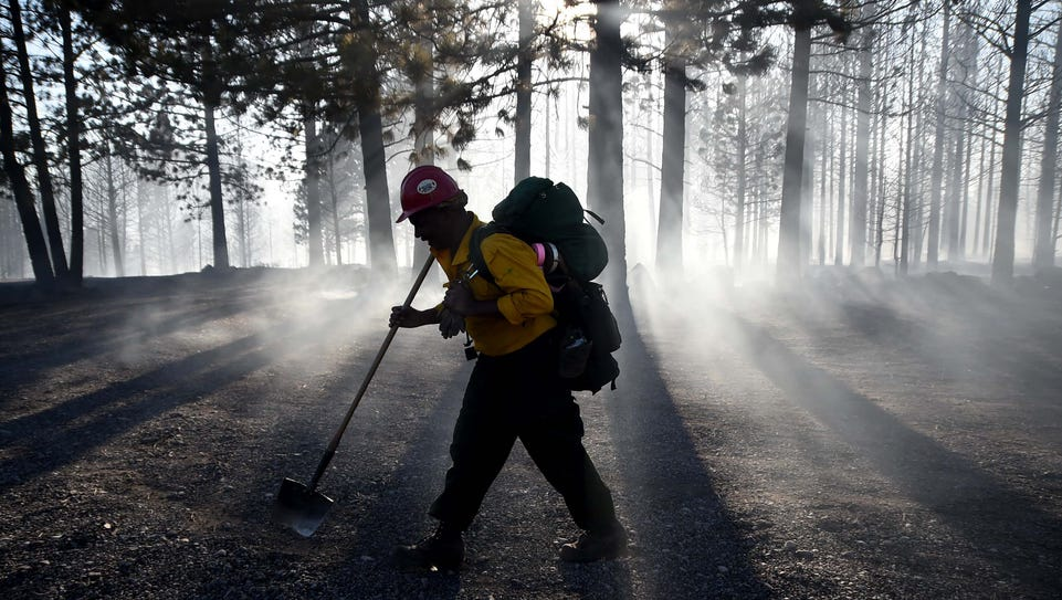 A firefighter walks through the smoke of a burned forest