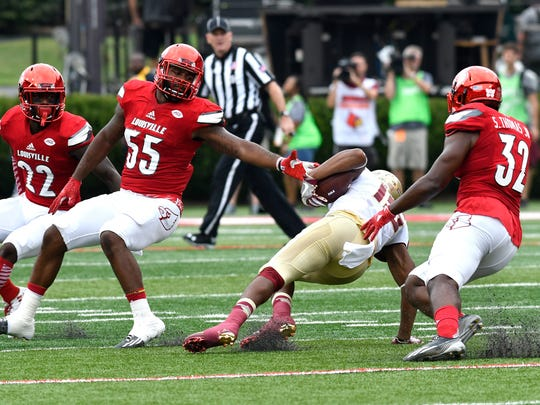 Florida State's Travis Rudolph (15) attempts to avoid the grasp of Louisville's Keith Kelsey (55) and Stacy Thomas (32) during the first quarter of an NCAA college football game, Saturday, Sep. 17, 2016 in Louisville Ky. (AP Photo/Timothy D. Easley)