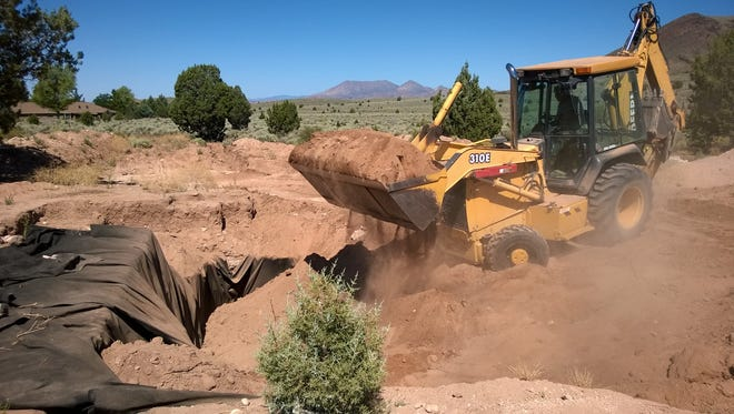 A backhoe operator works to fill back in an excavated pit house in Dammeron Valley on Friday, July 17.