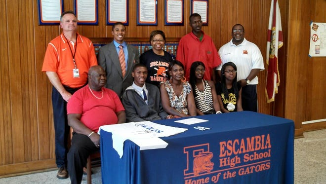 Jeremy Ruffin (back row, second from left) poses at a signing event for Demarlon Gardner Jr., after he signed a letter of intent to play basketball with Pensacola Christian College during a ceremony at Escambia High in 2014. Ruffin was hired as the Gators' boys basketball head coach on Thursday, June 8, 2017.