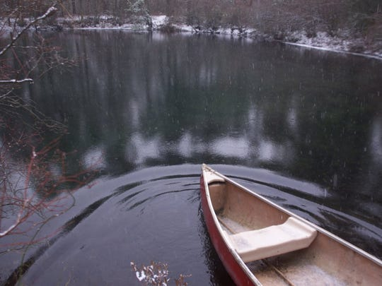 "A canoe gently slips into the waters of the Pine Barrens body of water known as the ""Blue Hole"" in Monroe Twp."