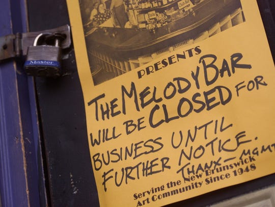A sign hangs on the padlocked front door of the Melody