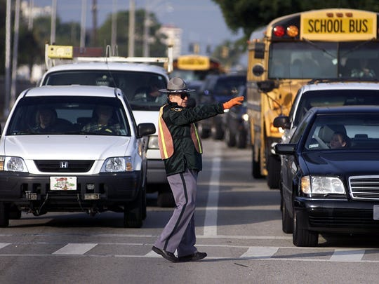 School buses wait in heavy traffic on Pine Ridge Road as a crossing guard holds back traffic.