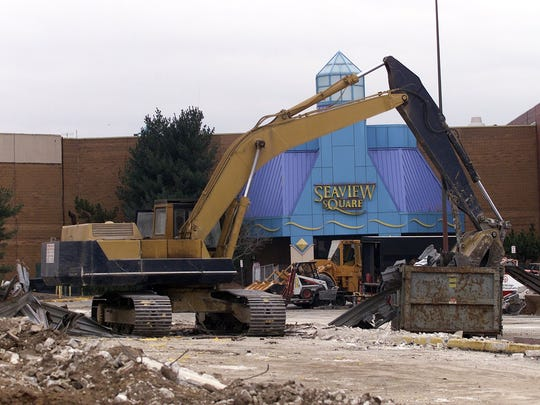 Construction vehicles work on demolishing the enclosed portion of the Seaview Square Mall in this 2001 file photo.