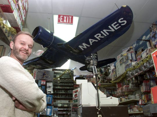 In this 1999 photo, Jackson Hobby Shop owner poses with a model airplane hanging at his store. After nearly 50 years in business, Gustafson is looking to sell or close the shop.