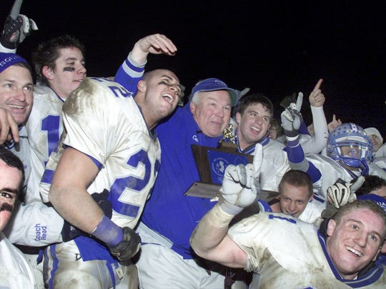 Manasquan head coach Vic Kubu, with Daniel Morgan (22) and teammates celebrate their 14-13 victory over New Brunswick in 2002 for the program's fifth straight state sectional title.