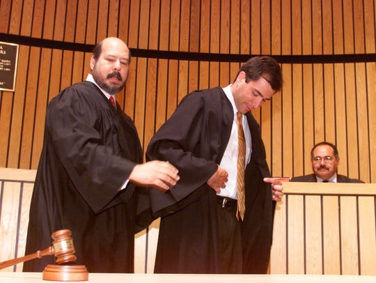 In this 2001 file photo, Judge Ariel Rodriguez gets the robe from Xavier Rodriguez, New Jersey Superior Court Appellate division.