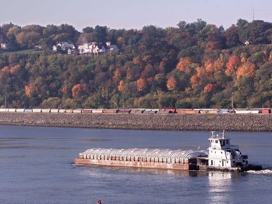TUGBOAT PUSHES A PAIR OF BARGES DOWNRIVER