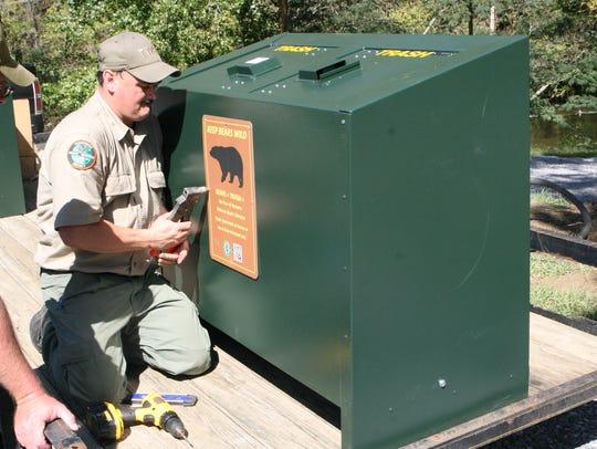 TWRA Dan Gibbs installs sign on newly build bear-proof