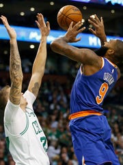 Boston Celtics' Daniel Theis (27) blocks a shot by New York Knicks' Kyle O'Quinn (9) during the first quarter of an NBA basketball game in Boston, Tuesday, Oct. 24, 2017.