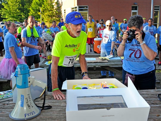 Peter Pressman blows out the candles on his birthday cake as his wife, Ruth, takes pictures Aug. 12 at McCabe Community Center in Nashville. He celebrated his 70th birthday with others at a community fun run/walk.