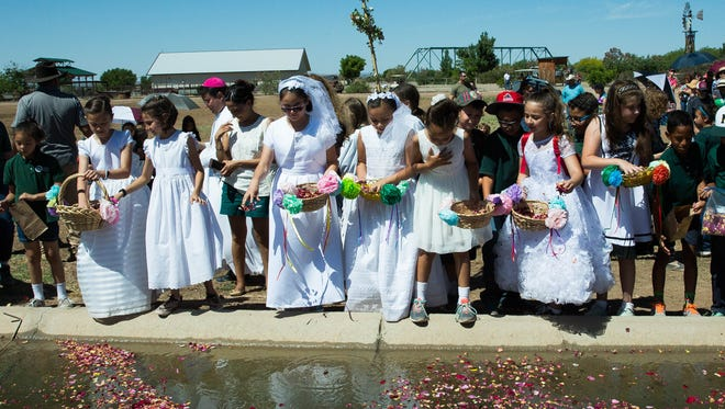 "Students from Holy Cross School, some in first communion dresses, drop rose petals into the irrigation canal at the New Mexico Farm and Ranch Heritage Museum, Monday May 15, 2017, during the last part of the blessing of the field ceremony at the Museum. The Blessing of the Fields, celebrates San Isidro Labrador or here in New Mexico known as ""San Ysidro"" the patron saint of farmers, this is the 19th year the blessing has taken place at the museum, it is lead by Bishop Oscar Cantú, stopping six times during the procession to bless different farm animals and areas of the museum grounds."