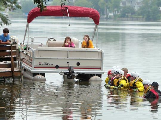 Neighborhood children watch from a dock and pontoon
