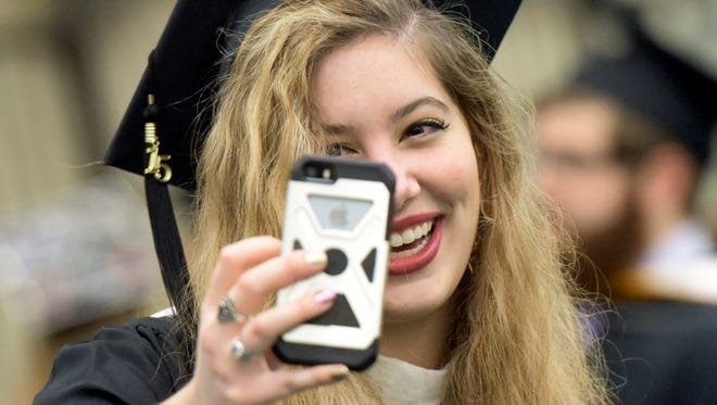 York College graduate Chelsea Monico of Hanover takes her pictures before the graduation ceremony at the college Tuesday, Dec. 22, 2015. The fine art/design major was one of almost 300 graduates in the winter commencement. York City Mayor Kim Bracey gave the address. (Bill Kalina - The York Dispatch)