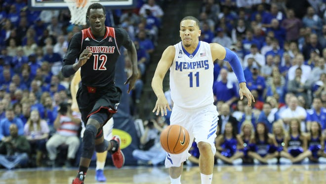 Memphis Tigers guard Michael Dixon Jr (11) drives past Louisville Cardinals forward Mangok Mathiang (12) at FedExForum. Memphis defeated Louisville 72-66.