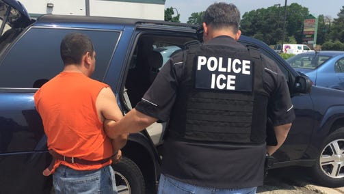 An Immigration and Customs Enforcement officer detains a man in the Midwest.