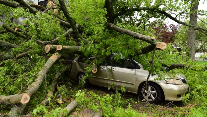 An uprooted tree fell on a house and car at a home on Bernard Place in Ho Ho Kus on Wednesday May 16, 2018. One person was trapped in the car for one and a half hours while they waited for PSE&G to cut the power to the live wires that fell around the car, according to Lisa Brummel, a neighbor.