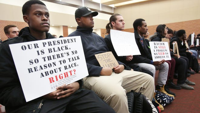 University of Wisconsin-Madison sophomore Marquise Mays, left, and sophomore Jerad Maxberry, along with other students, hold up signs protesting racism on campus during a meeting for the UW System Board of Regents on campus in Madison on Friday.