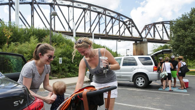 """Kate Cope, from left, pulls her daughter Allie Cope out of her stroller with friend Candice Lofton after a walk across the Big Four Pedestrian Bridge Thursday. Cope and Lofton both enjoy visiting the bridge with family and pets to get outside for exercise, but aren't happy to hear that soon they may be charged for parking. """"If they were to start charging for parking that would definitely curtail our ability to come,"""" Lofton said. """"Part of the attraction is that it's free and it's accessible to everyone."""" Cope echoed Lofton in her sentiments. """"If they start charging I'm not sure I would continue to come here,"""" Cope said. """"Three hours seems like more time than I usually spend, so I'm not sure I'd be willing to pay three dollars."""" Aug. 24, 2016"""
