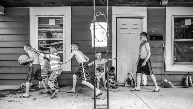 Brothers Joshua Gaither, 14, Theo Patrick Johnson III, 11, Chad Johnson, 8, and Jacob Ryan Johnson, 7, play porch basketball at their home in Near West on Thursday, July 6, 2017.