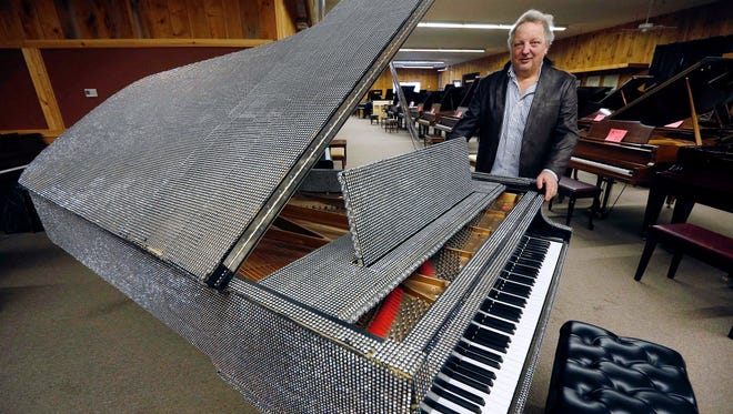 In this Saturday, Jan. 24, 2015 photo, Rob Norris, owner of the Piano Mill in Rockland, Mass., stands beside a piano once owned by Liberace. A section of roof collapsed into the music store's showroom under the weight of snow Tuesday, Feb. 10, 2015. Norris said it is unclear if the Liberace piano was damaged.