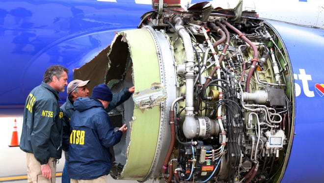 """A National Transportation Safety Board investigator examines damage to the engine of Southwest Airlines Flight 1380 that made an emergency landing at Philadelphia International Airport in Philadelphia. A preliminary examination of the blown jet engine of the Southwest Airlines plane that set off a terrifying chain of events and left a businesswoman hanging half outside a shattered window showed evidence of """"metal fatigue,"""" according to the National Transportation Safety Board."""