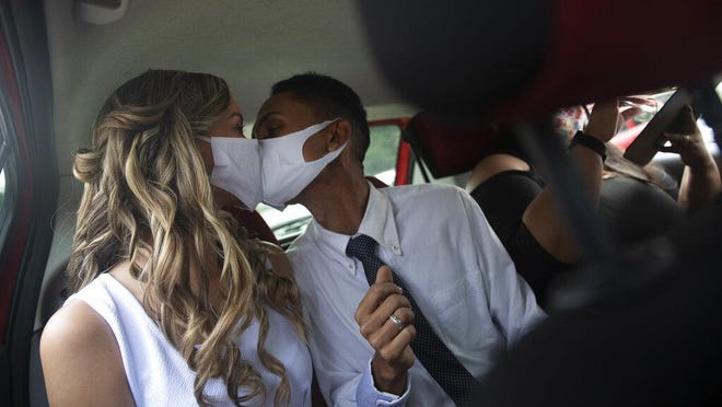 Wearing masks to prevent the spread of the new coronavirus, Thiago do Nascimento, right, and Keilla de Almeida kiss during their drive-thru wedding at the registry office in the neighborhood of Santa Cruz, Rio de Janeiro, Brazil on May 28. Couples have begun turning to this unconventional union at a notary in Santa Cruz since the COVID-19 started battering Brazil.