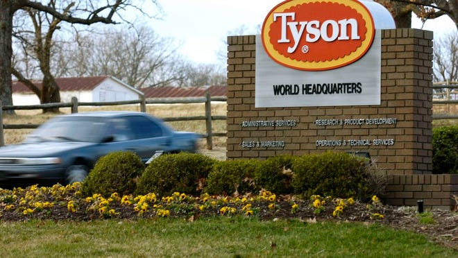 FILE - In this Jan. 29, 2006, file photo, a car passes in front of a sign at Tyson headquarters in Springdale, Ark. The union representing workers at poultry processing plants sued the federal government on Tuesday, July, 28, 2020, to challenge a new rule that allows companies to increase line speeds through a waiver permitted by the U.S. Department of Agriculture. The United Food and Commercial Workers International Union and local unions representing plants in Alabama, Arkansas, Indiana, Kentucky, Mississippi and Missouri joined with nonprofit consumer advocacy group Public Citizen to file the lawsuit in federal court in Washington.