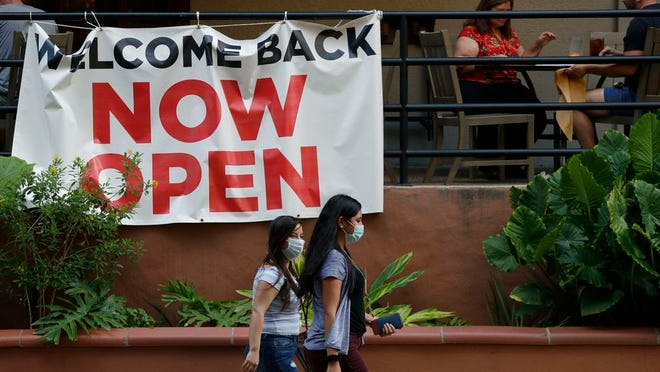 In this May 27, 2020, file photo, visitors to the River Walk pass a restaurant that has reopened in San Antonio. Coronavirus cases are rising in nearly half the U.S. states, as states are rolling back lockdowns.