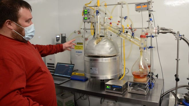 """Sunflower Hemp Co. owner Colby Terlip explains how his short-path distillation, or fractional distillation, system works. """"It's basically like a fancy moonshine still,"""" he said."""