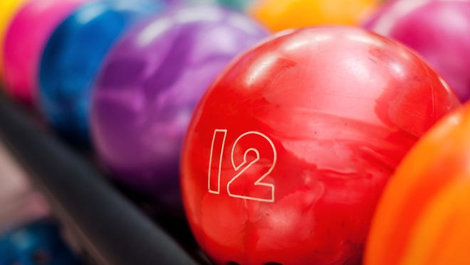 Close-up of bright red bowling ball lying in the rows of other colorful balls