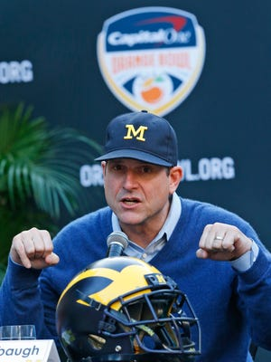 Michigan football coach Jim Harbaugh gestures as he talks during a news conference on Dec. 7, 2016 in Hollywood, Fla.