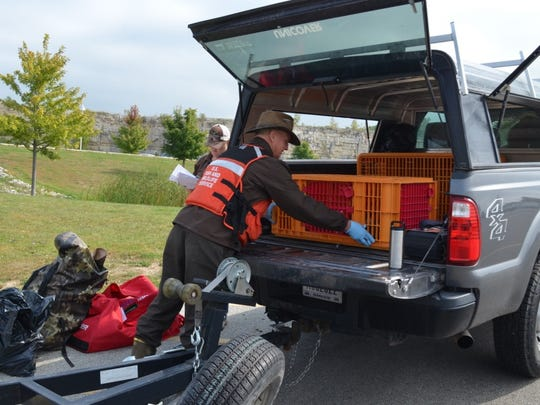 A member of the U.S. Fish and Wildlife Service loads