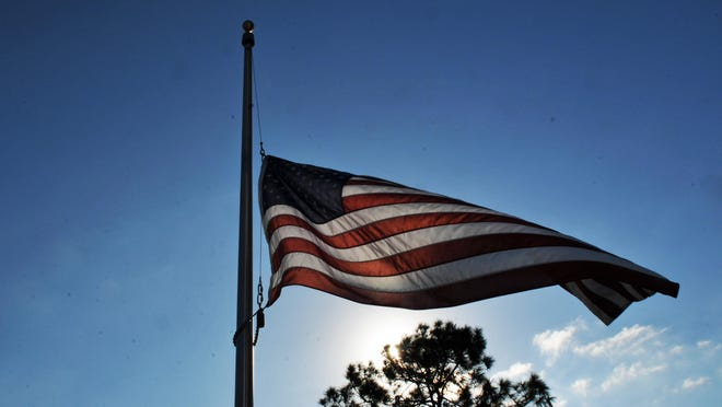 The flag flies at half staff over Cape Canaveral National Cemetery.