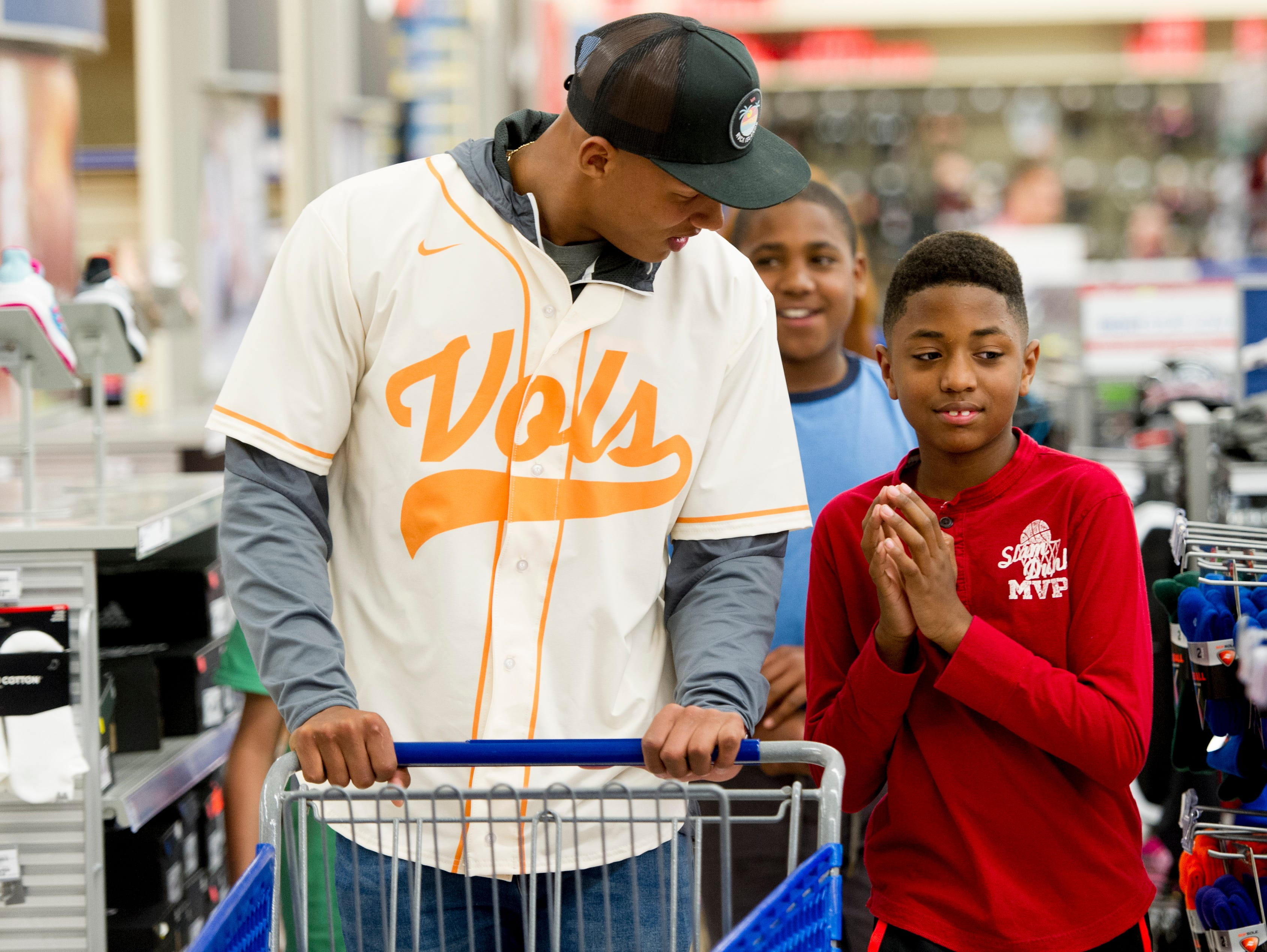 Former UT QB Joshua Dobbs chats with Jabari Isom, 11, of Knoxville, while pushing a shopping cart full of football gear during a football sporting goods shopping spree at Academy Sports + Outdoors in Knoxville, Tennessee on Friday, March 31, 2017. Dobbs held a shopping spree for 11 area kids who are participating in his football camp.