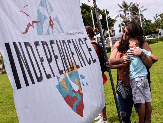 In this July 4, 2017, file photo, Vicente Taimanglo-Ventura is hugged by his mother, Desiree Taimanglo-Ventura, during the Na'lå'la Songs of Freedom concert at Adelup.