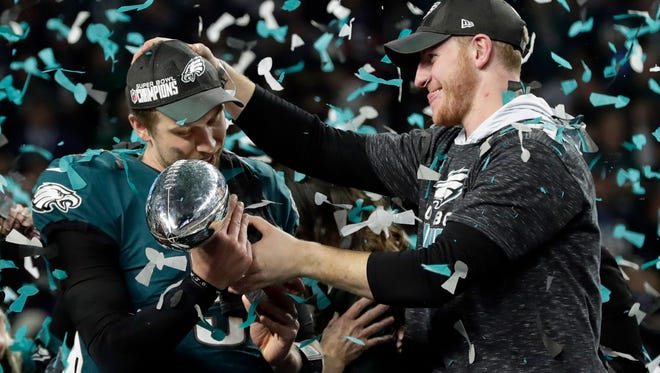 Philadelphia Eagles quarterback Carson Wentz, right, hands the Vincent Lombardi trophy to Nick Foles after winning the NFL Super Bowl 52 football game against the New England Patriots in Minneapolis. The Eagles won 41-33.