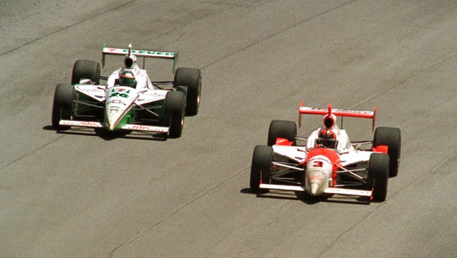 THE DISPUTED PASS...(left to right) Paul Tracy, in car number 26, passing (on the outside) number 3, Helio Castroneves...At the end of the race.