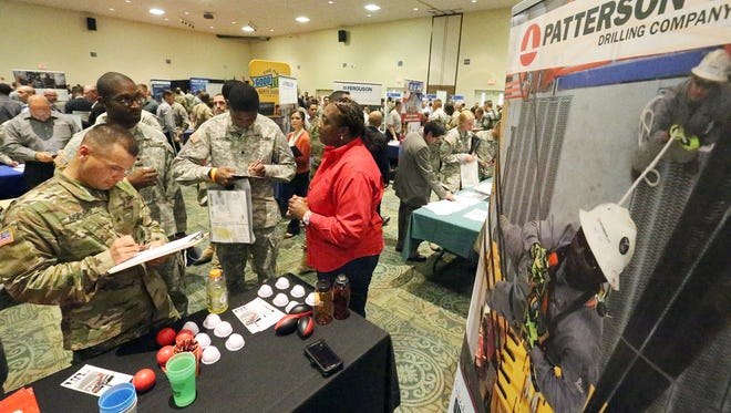 """A representative of Patterson-UTI Drilling talks with Army soldiers at a previous Fort Bliss job fair. The annual """"Hiring Red, White and You!""""  job fair will be held Thursday at the Army post."""