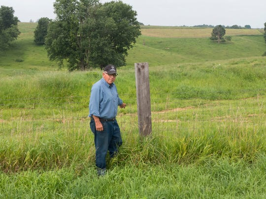 Gerry Weiss in front of a landscape he began healing almost 40 years ago. Terraces like the one right behind the fence, waterways like the draw at right-center, and permanent grass cover all prevent erosion on these steep slopes near Lancaster, Wisconsin.