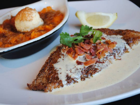 The bacon and pecan crusted redfish with orange beurre blanc and a side of sweet potato creme brulee is one of the options you'll find at Half Shell Oyster House.