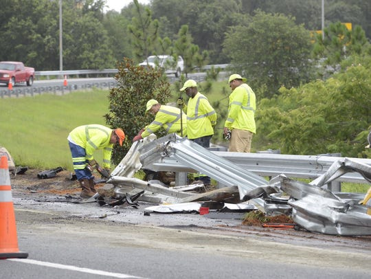 Workers clean up after an accident on the ramp from