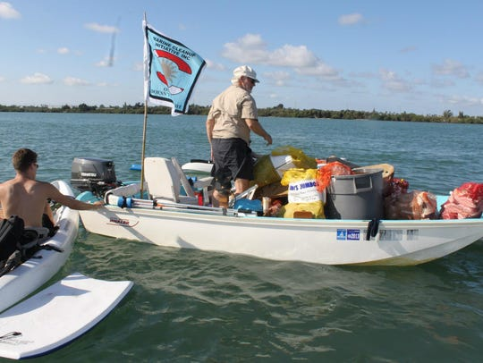 A volunteer with Marine Cleanup Initiative Inc. helps