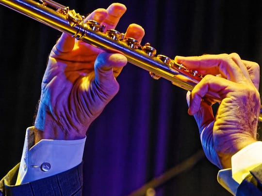 A close up view of playing the flute gives an image of the fingering while playing as Alexander Zonjic, renowned flutist plays along with his band. He named his flute Goldie.