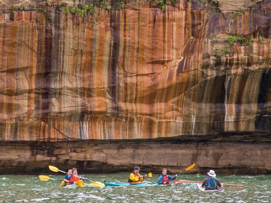 Kayakers paddle past the Pictured Rocks National Lakeshore.