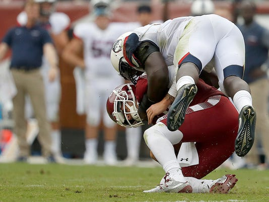 Temple's Logan Marchi, left, is sacked by Connecticut's Junior Joseph, right, during the third quarter of an NCAA college football game in Philadelphia, Pa., Saturday, Oct. 14, 2017. (David Maialetti/The Philadelphia Inquirer via AP)