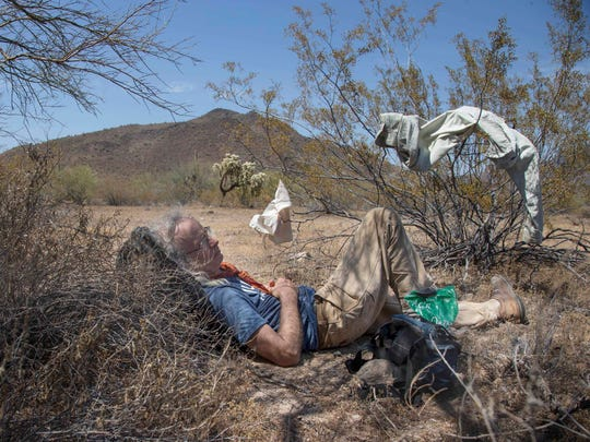 A volunteer with the humanitarian group No More Deaths rests June 23, 2017, after a search for remains of migrants who died in remote rugged terrain while crossing the U.S. border in triple-digit temperatures through the Organ Pipe Cactus National Monument near Ajo, Ariz.