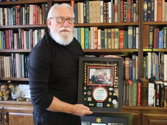 Ray Swadley Jr. holds one of the framed photos given